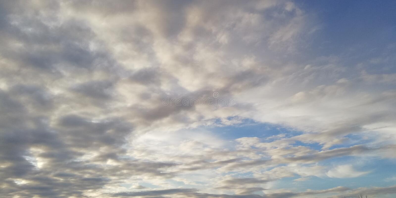 The battle of light and darkness. Light white clouds and dark clouds in the blue sky. Interesting unusual background royalty free stock images