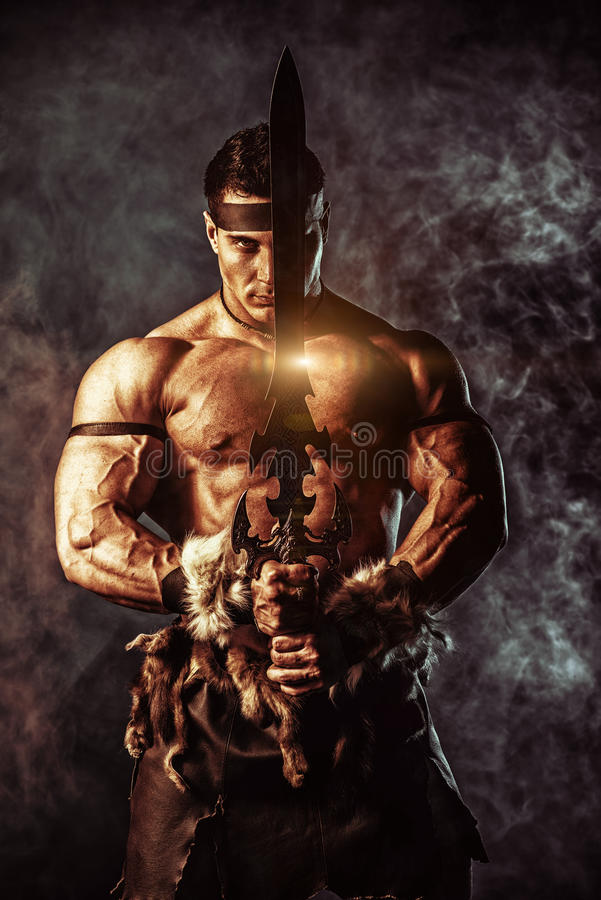 Battle man. Portrait of a handsome muscular ancient warrior with a sword stock photos