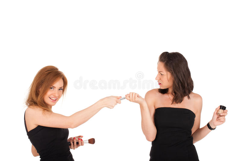 Battle for mascara. Two young ladies are fighting for mascara stock photography