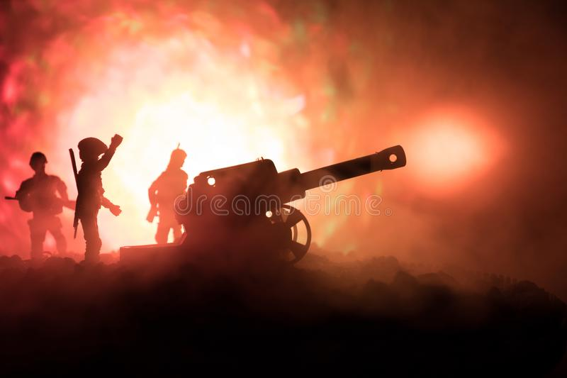 Battle scene with arillery and standing soldiers. Silhouette of old field gun standing at field ready to fire. With colorful dark stock photo