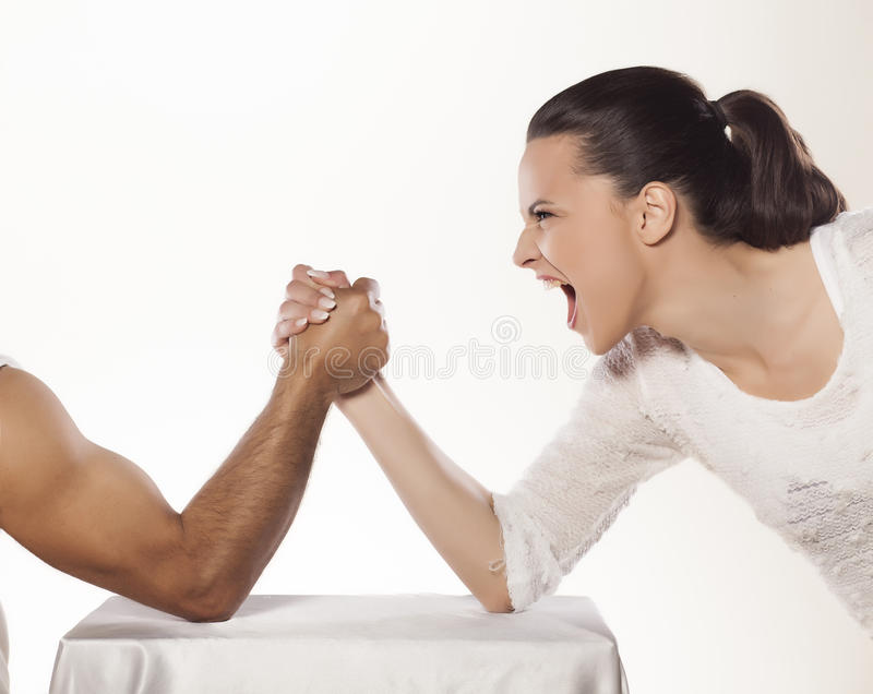Battle of the sexes. Angry girl arm wrestles with a man royalty free stock image