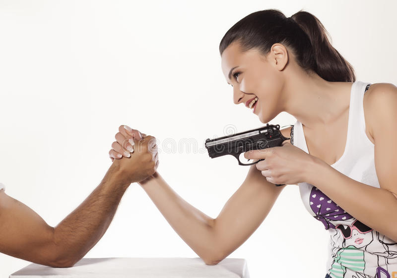 Battle of the sexes. Smiling girl arm wrestles with a man and holds a gun stock images