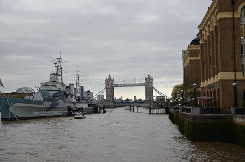 Battle ship by tower bridge on the river thames in london. England, united kingdom royalty free stock image
