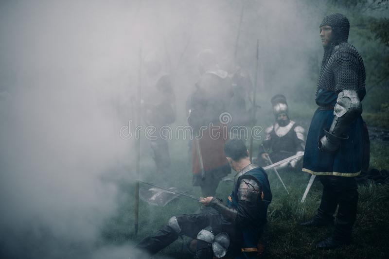Battle squad of medieval knights of the Crusaders rest in a misty forest. Battle squad of medieval knights of the Crusaders rest on the halt against background royalty free stock photos