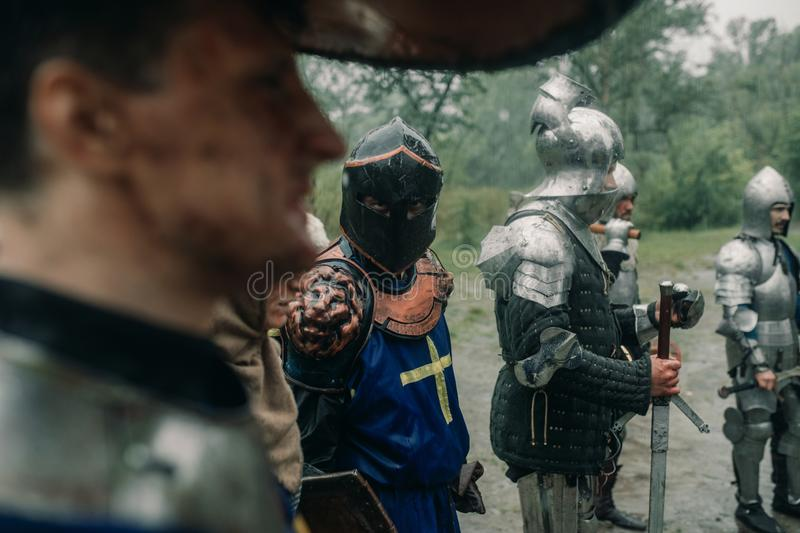 Battle squad of medieval knights of the Crusaders stand with their swords. Battle squad of medieval knights of the Crusaders stand in armors and helmets with royalty free stock images