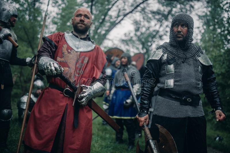 Battle squad of medieval knights of the Crusaders with weapons. Battle squad of medieval knights of the Crusaders with spears, swords and axes royalty free stock photo