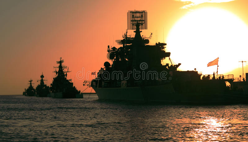 Battle sunset. Warships lined up in a bay at sunset with a large sun which forms a gradient of bright colors of yellow and red tones