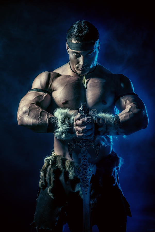 Battle time. Portrait of a handsome muscular ancient warrior with a sword stock image