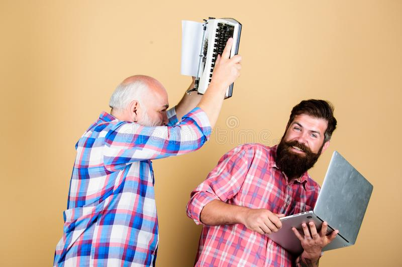 Battle time. retro typewriter vs laptop. New technology. technology battle. Modern life. father and son. family royalty free stock photo