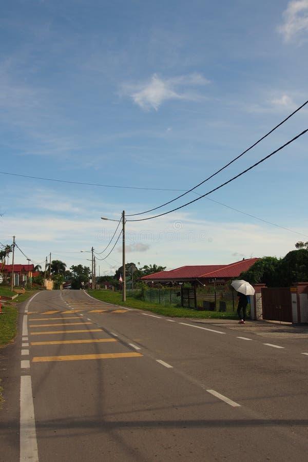 Batu Arang town. A pedestrian with umbrella walking on the street in Batu arang old town royalty free stock image