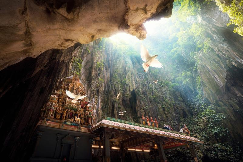 Batu Cave temple. Within cave and bird fly under light from the top, Hindu cave in Kuala Lumpur, Malaysia stock image