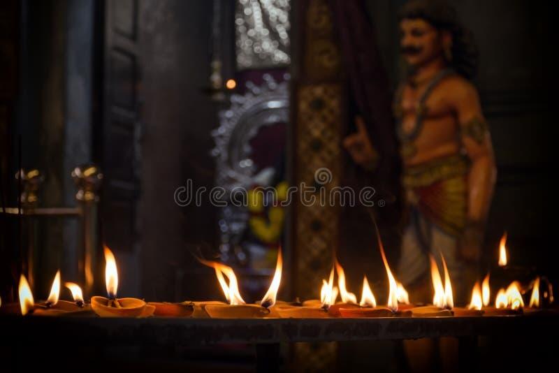 Batu interior excava en Kuala Lumpur - llama de las velas sagradas del ritual del aceite, en el fondo de la estatua de Krishna imagen de archivo libre de regalías