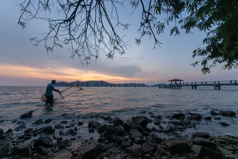 Fisherman cast net in evening. Batu Kawan, Penang/Malaysia - Mar 06 2017: Fisherman cast net in evening royalty free stock photography