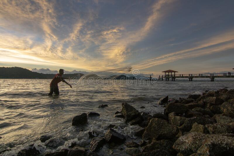 Fisherman cast net near rock coastal in sunset hour. Batu Kawan, Penang/Malaysia - Mar 21 2017: Fisherman cast net near rock coastal in sunset hour stock image