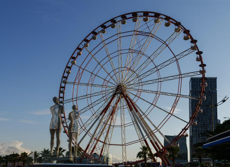 Batumi,Adjara,Georgia - July 06 2019, Batumi embankment, Ferris wheel in the rays of the setting sun, on the background. Batumi,Adjara,Georgia - July 06 2019 royalty free stock photos