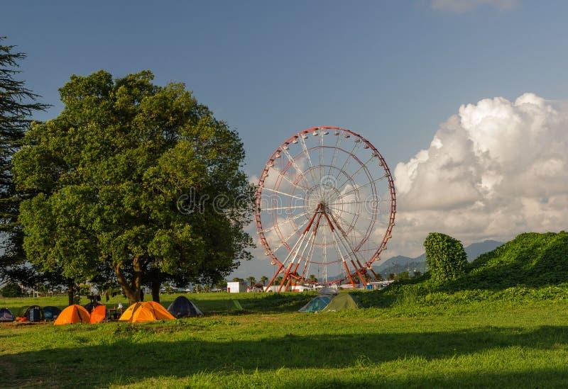 Batumi,Adjara,Georgia - July 06 2019, Batumi embankment, Ferris wheel in the rays of the setting sun, in the foreground on the. Batumi,Adjara,Georgia - July 06 stock images
