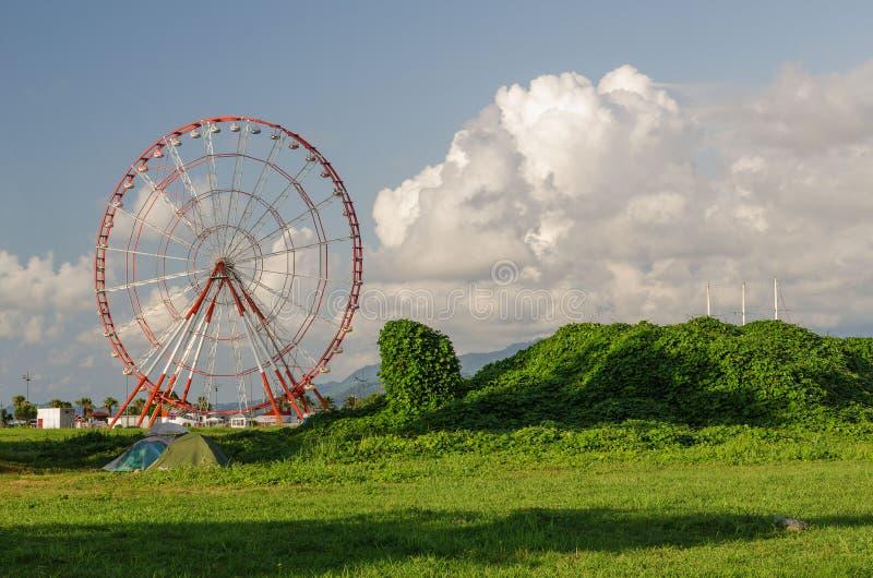 Batumi,Adjara,Georgia - July 06 2019, Batumi embankment, Ferris wheel in the rays of the setting sun, in the foreground. Batumi,Adjara,Georgia - July 06 2019 royalty free stock photo