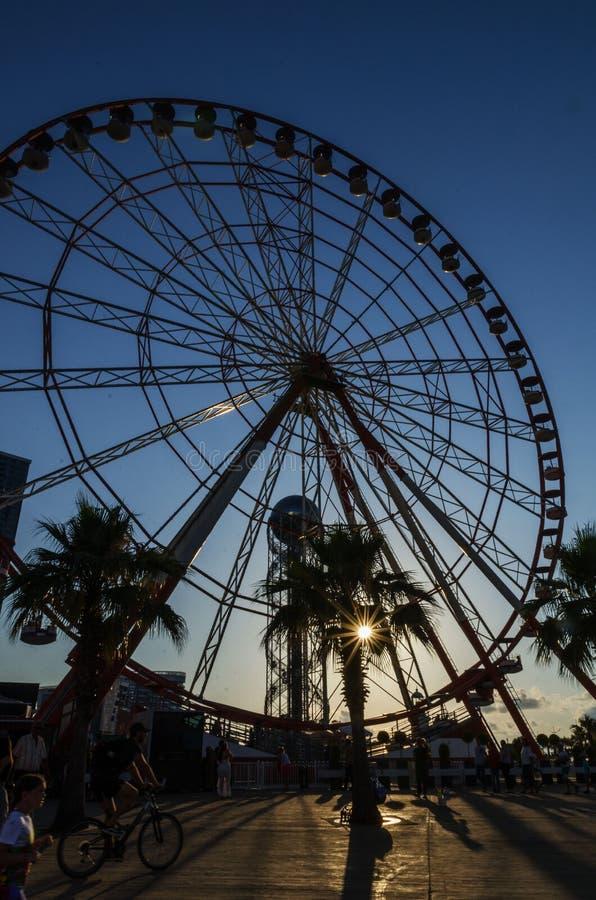 Batumi,Adjara,Georgia - July 06 2019, Batumi embankment, Ferris wheel in the rays of the setting sun. The rays of the sun make their way through the supports stock photo