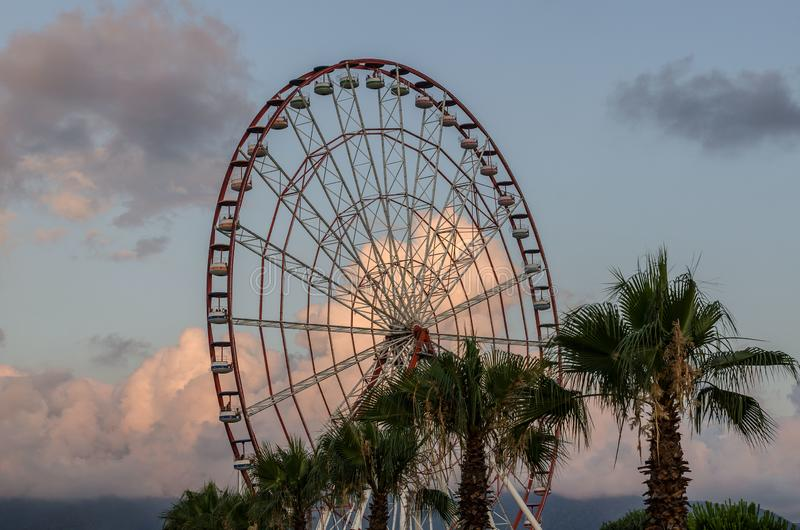 Batumi,Adjara,Georgia - July 06 2019, Batumi embankment, Ferris wheel in the rays of the setting sun, unusually colored clouds. Batumi,Adjara,Georgia - July 06 royalty free stock photo