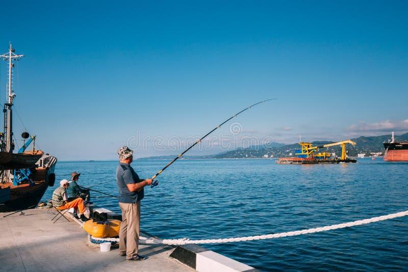 Batumi, Adjara, Georgia Uomo anziano che pesca vicino al bacino del porto su soleggiato fotografia stock libera da diritti