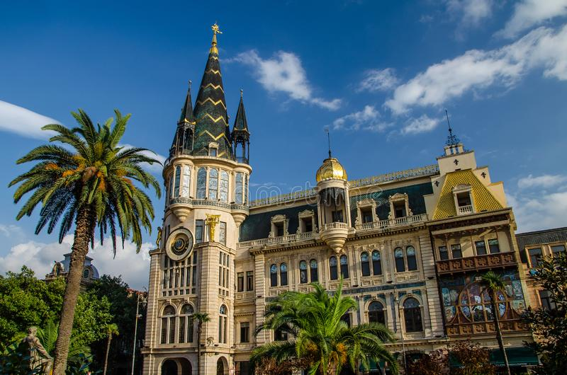 Batumi Astronomical Clock Tower building with palm tree and blue sky with few clouds above stock image