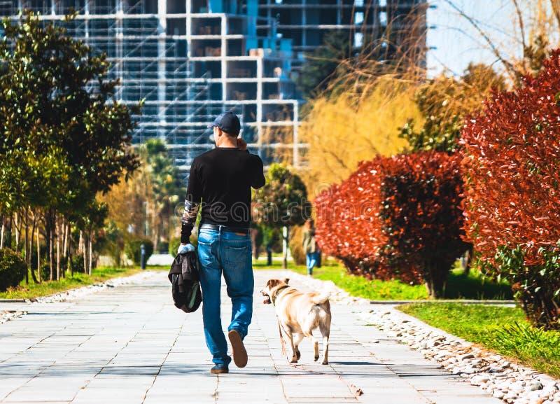 Batumi, Georgia - aprile, 09 del 2019 Un uomo ed il suo cane per una passeggiata nel parco fotografia stock