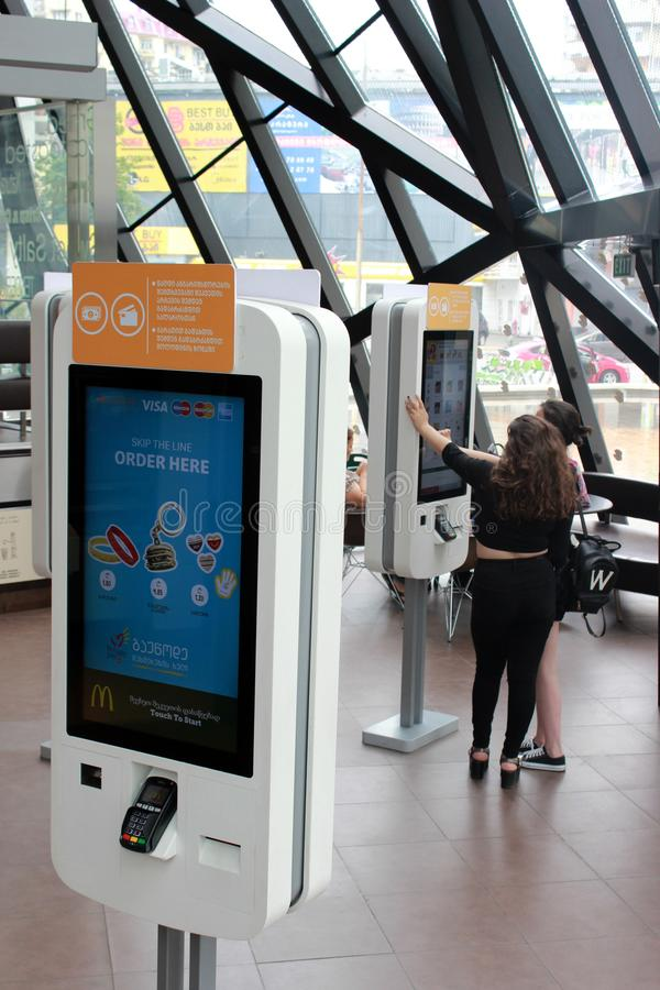 Batumi, Georgia - June 2019: Two dark-haired girls are purchasing fast-food from online self service McDonalds terminal. stock photo