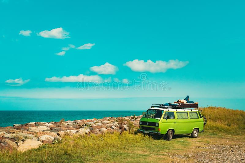 Batumi, Georgia - September 14, 2018: Young male lying on top of the green old timer classic camper van parked near the sea shore stock images
