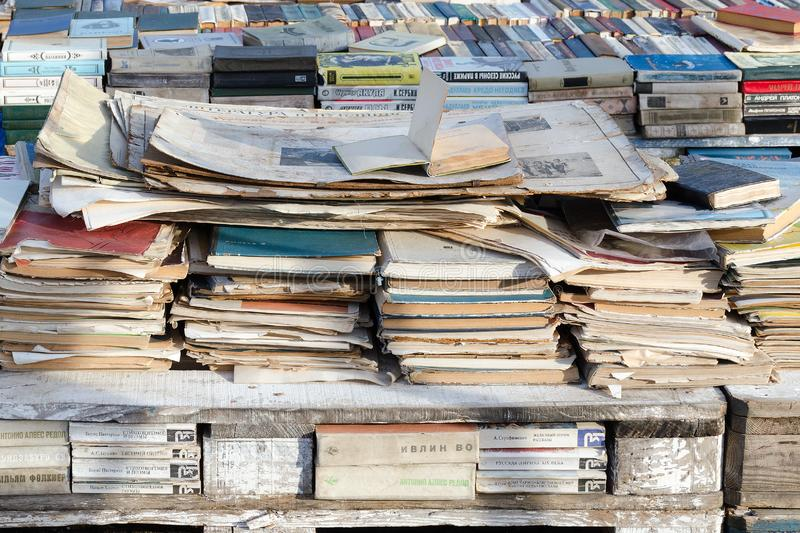 Vintage, battered russian books and papers are stacked on counter, selling old books, close up. royalty free stock photography