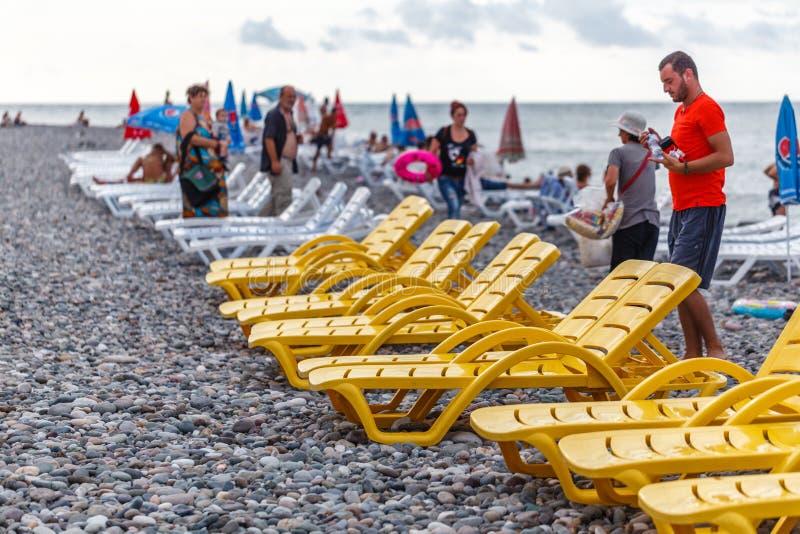 """BATUMI, GRUZJA †""""SIERPIEŃ 02, 2018: wietrzeje gdy ty no może pływać w lecie, puści pokładów krzesła na plaży obraz royalty free"""