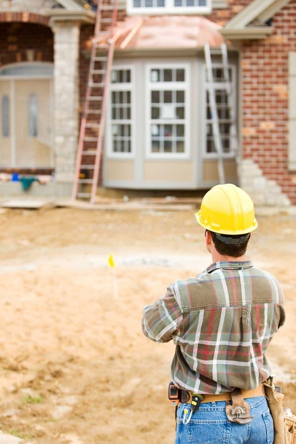 Bau: Arbeitskraft betrachtet neues Haus lizenzfreie stockfotos