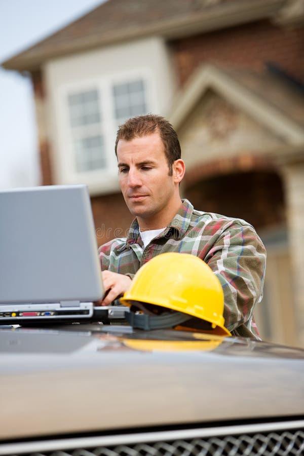 Bau: Auftragnehmer, der Laptop für Arbeit verwendet stockfotografie