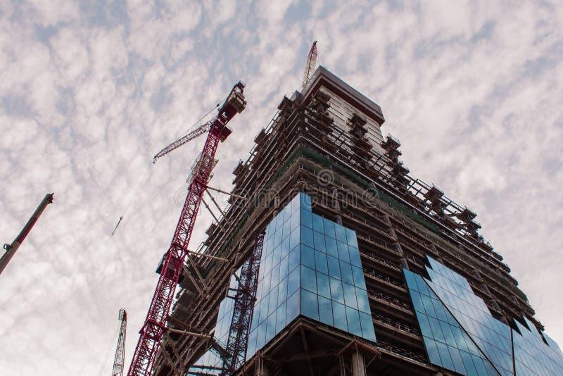 Bau des hohen Gebäudes Baukräne und -wolkenkratzer stockfotografie