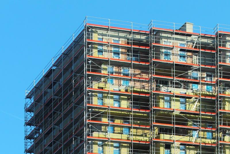 Bau eines hohen mehrstöckigen Gebäudes Wolkenkratzer versorgt mit Metallbaugerüst Gefährliche Arbeit auf Höhe Modernes Archit stockfotografie