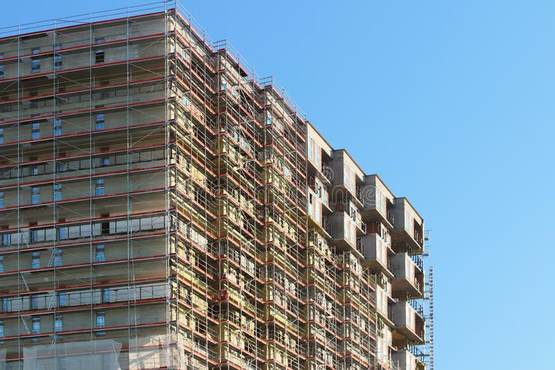 Bau eines hohen mehrstöckigen Gebäudes Wolkenkratzer versorgt mit Metallbaugerüst Gefährliche Arbeit auf Höhe Modernes Archit lizenzfreies stockfoto