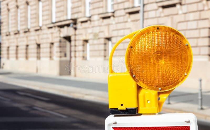 Bau-Sicherheit Straßenbarrikade mit Warnsignallampe auf einer Straße, Unschärfegebäudehintergrund lizenzfreies stockbild