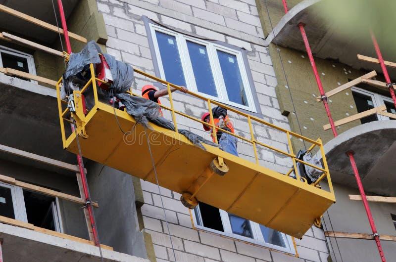 Bau verschobene Wiege mit Arbeitskräften auf einem eben errichteten hohen Gebäude lizenzfreie stockfotografie