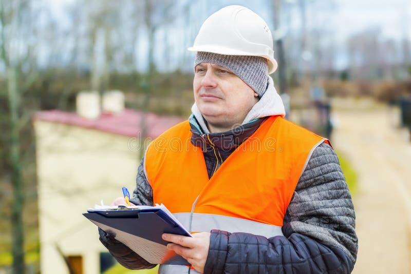 Bauangestellter mit Dokumentation nahe Gebäude stockbilder