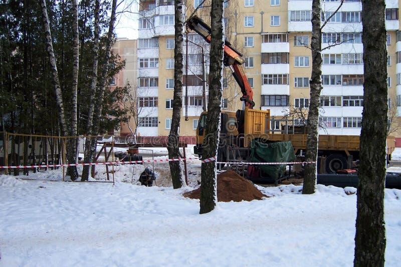 Bauarbeiten, der Last-anhebende Kran des Automobils, LKW-Kranpfeil vor dem hintergrund der Bäume, Winter, die Stadt, stockbilder