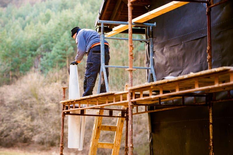 Bauarbeiter auf dem Gestell, das thermisch Haus, blac isoliert stockfotografie