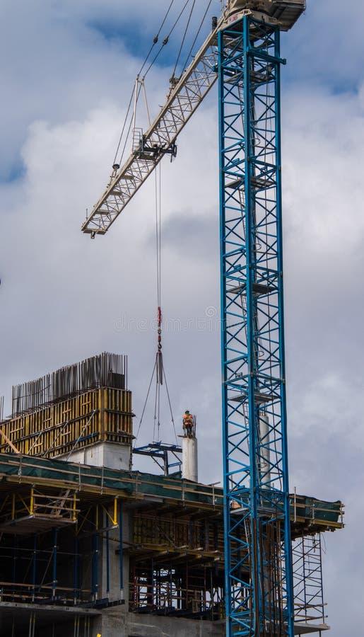 Bauarbeiter auf konkrete Säule mit Kran lizenzfreie stockfotos