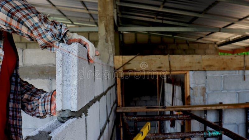 Bauarbeiter bauen Mauern aus Ziegelstein stockbilder