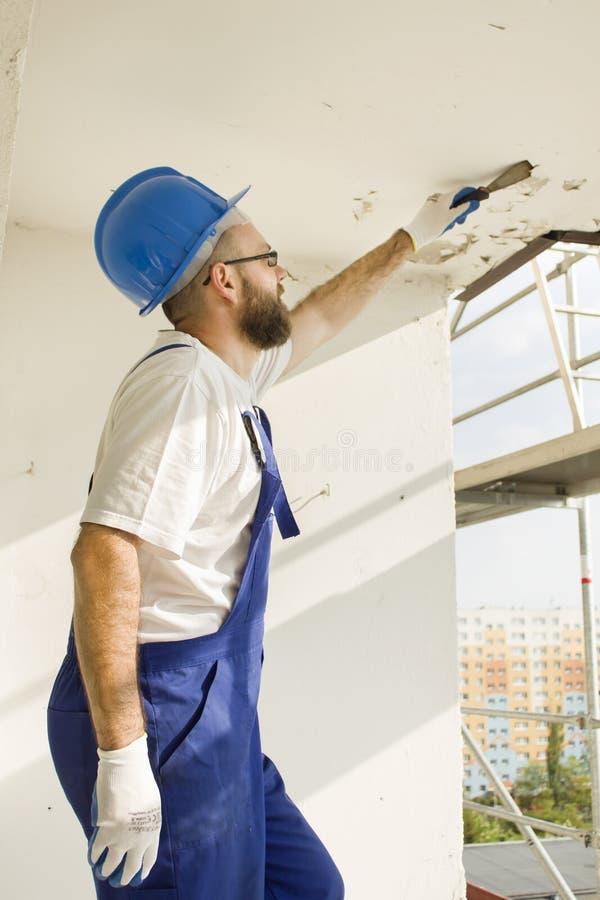 Bauarbeiter in der Arbeitskleidung, in den Schutzhandschuhen und in einem Sturzhelm auf Standort Entfernen Sie die alte Farbenspa stockbilder