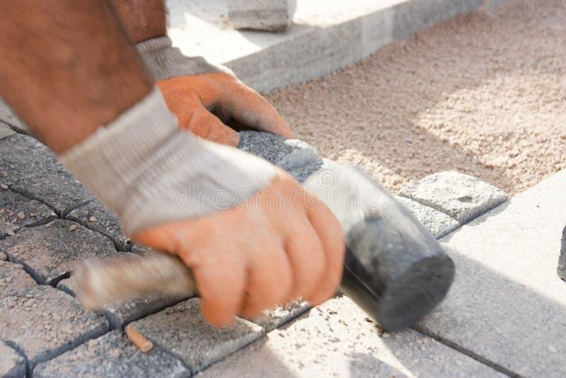 Bauarbeiter, der clobble Steine im Sand legt stockfotos