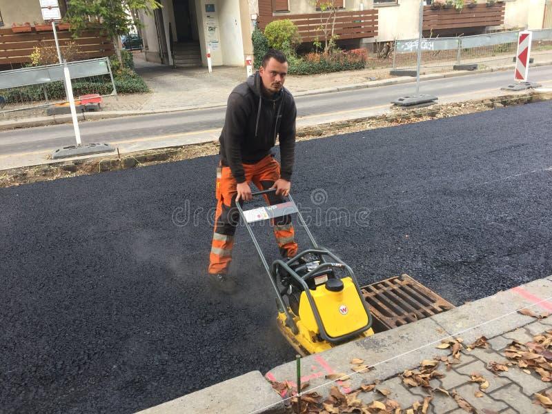 Bauarbeiter, der ein Plattenverdichtungsgerät verwendet lizenzfreie stockfotos