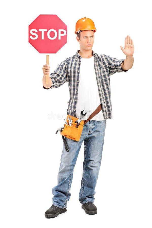 Bauarbeiter, der ein Stoppschild hält lizenzfreies stockfoto