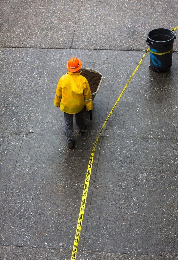 Bauarbeiter, der eine Schubkarre auf der Straße drückt lizenzfreie stockfotos