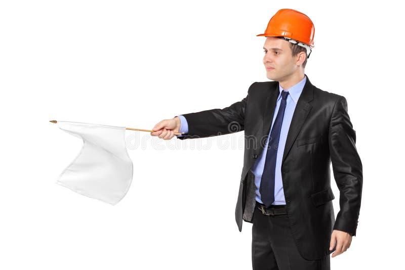 Bauarbeiter, der eine weiße Flagge wellenartig bewegt lizenzfreie stockbilder