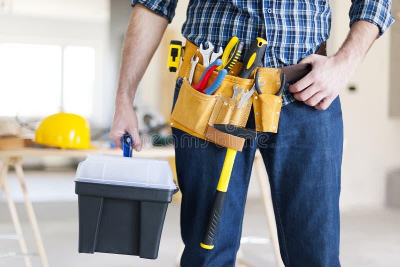 Bauarbeiter, der einen Werkzeugkasten hält lizenzfreie stockbilder