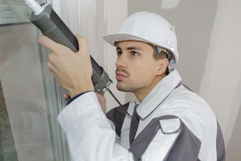 Bauarbeiter, der Fenster in Haus installiert lizenzfreies stockbild